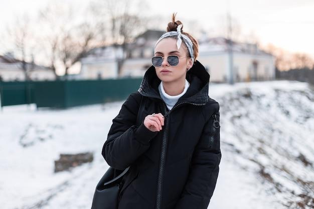Giovane donna alla moda bella hipster in occhiali da sole neri in un'elegante bandana in una giacca nera alla moda con uno zaino pone all'aperto su uno sfondo di colline innevate.