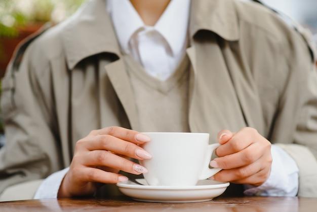 Giovane bella donna alla moda che si siede nel caffè della città in strada
