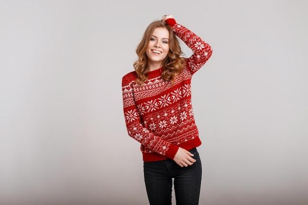 Giovane bella donna alla moda in un maglione lavorato a maglia rosso alla moda con una stampa su uno sfondo grigio