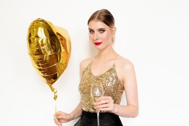 Giovane donna bionda alla moda in canotta di paillettes glamour e gonna nera in organza che tiene un palloncino a forma di cuore e un flûte di champagne