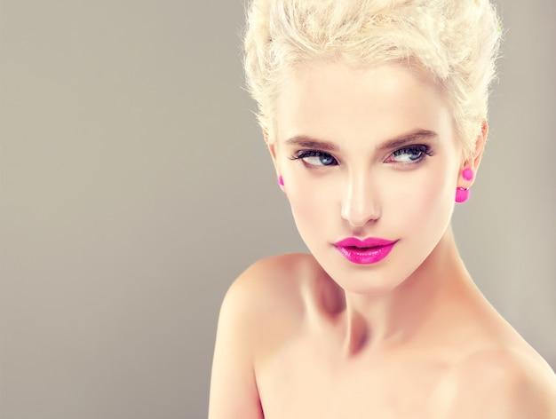 Giovane ragazza dai capelli bionda alla moda con taglio di capelli corto alla moda sulla testa, sta dimostrando trucco alla moda e luminoso con rossetto rosa vivido. arte dell'acconciatura, cura dei capelli e trucco.
