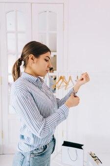 La giovane donna alla moda di affari raddrizza la sua camicia, preparandosi per un evento importante. realizzazione carriera ricchezza concetto aziendale.