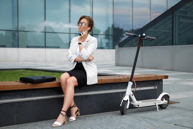 Giovane ed elegante imprenditrice fumare vape dopo il suo lavoro
