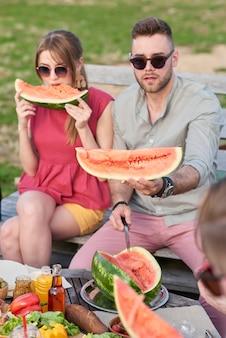 Giovani coppie caucasiche alla moda che mangiano anguria matura all'aperto mentre sono in giro con gli amici la sera d'estate