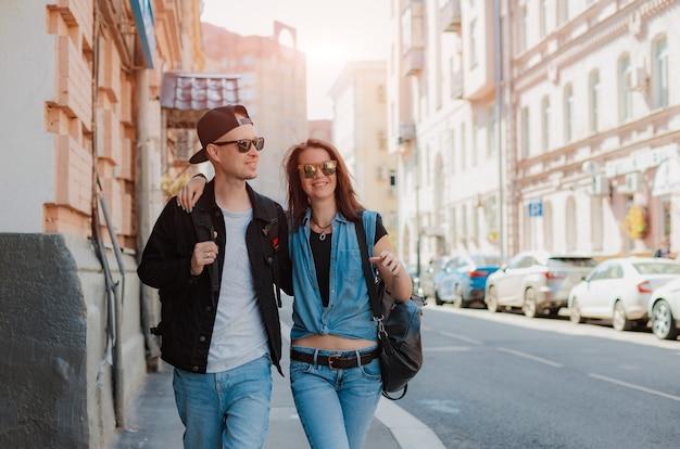 La giovane coppia alla moda cammina intorno alla città con gli occhiali da sole. cammina per appuntamenti con un ragazzo