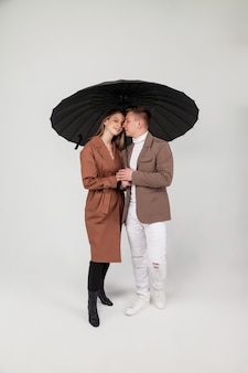 La giovane coppia alla moda con l'ombrello nero mostra le emozioni d'amore. ritratto di persone emotivamente carine in abiti autunnali in piedi sotto l'ombrello mentre guardano su uno sfondo grigio chiaro. copia spazio per il sito