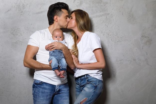 Famiglia giovane ed elegante. felice madre e padre con bambino piccolo.