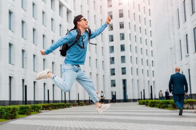 Il giovane ragazzo alla moda in vestiti blu salta vicino a un edificio moderno bianco