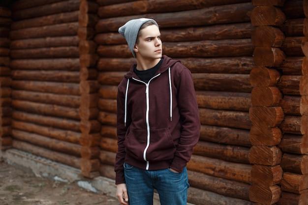 Giovane ragazzo alla moda vicino a una casa in legno