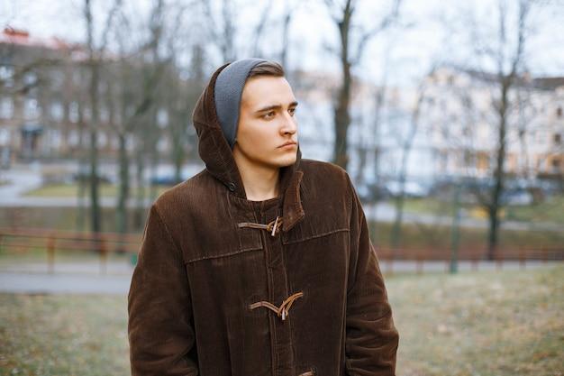 Giovane ragazzo alla moda in una vecchia giacca e berretto in maglia nella sosta di autunno
