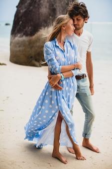 Giovani coppie alla moda hipster nell'amore sulla spiaggia tropicale durante le vacanze