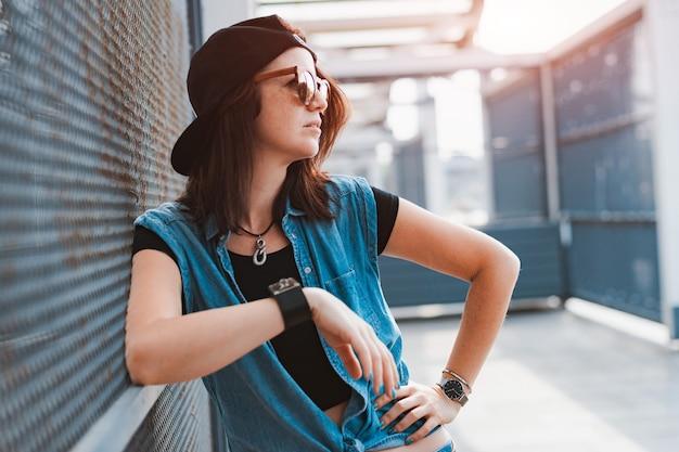 Giovane ragazza alla moda hipster in un'immagine audace in un berretto e occhiali da sole posa in città sotto i raggi del tramonto