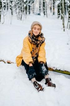 Giovane ragazza alla moda hipster in giacca gialla che si siede sul legno nella foresta di neve