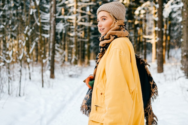 Giovane ragazza alla moda hipster in giacca gialla con una sciarpa calda in posa nella foresta di neve
