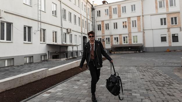 Giovane uomo alla moda hipster in occhiali da sole in una giacca di pelle in jeans con uno zaino cammina per strada vicino a edifici d'epoca. modello alla moda in abiti oversize si gode una passeggiata in una giornata primaverile.