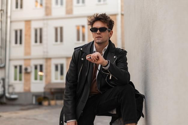 Il giovane hipster alla moda in abbigliamento alla moda in occhiali da sole d'annata sta riposando e gode della nicotina vicino al muro sulla strada. il simpatico ragazzo americano fuma una sigaretta all'aperto. abitudine rilassante ma dannosa.