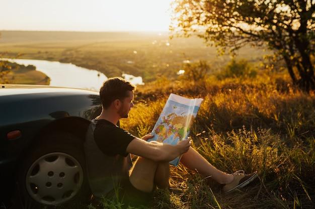 Giovane uomo alla moda che tiene la mappa vicino alla sua auto sul tramonto.