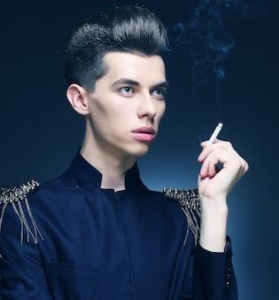 Giovane uomo alla moda che fuma una sigaretta. colpo dello studio.