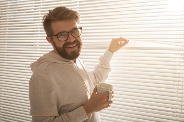 Giovane uomo alla moda con barba e caffè che dà una occhiata attraverso il foro nelle persiane delle finestre e guardando fuori