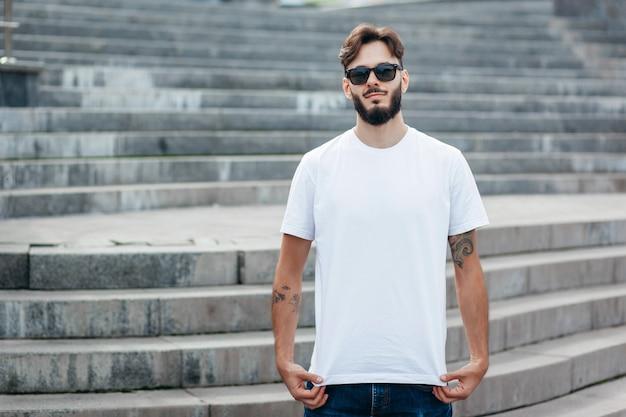 Un giovane uomo alla moda con la barba in maglietta bianca e occhiali