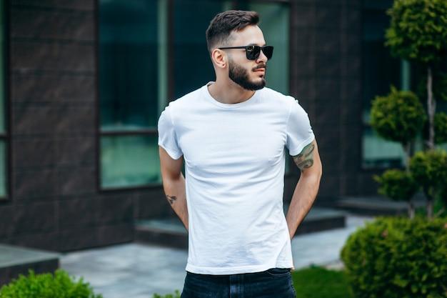 Un giovane uomo alla moda con la barba in una maglietta bianca e occhiali da sole
