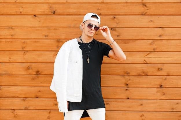 Giovane uomo alla moda con occhiali da sole in una giacca bianca e una maglietta nera con un berretto da baseball vicino alla parete in legno