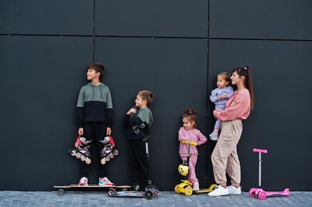 Giovane madre alla moda con quattro bambini all'aperto contro il muro moderno nero. la famiglia sportiva trascorre il tempo libero all'aperto con scooter e pattini.