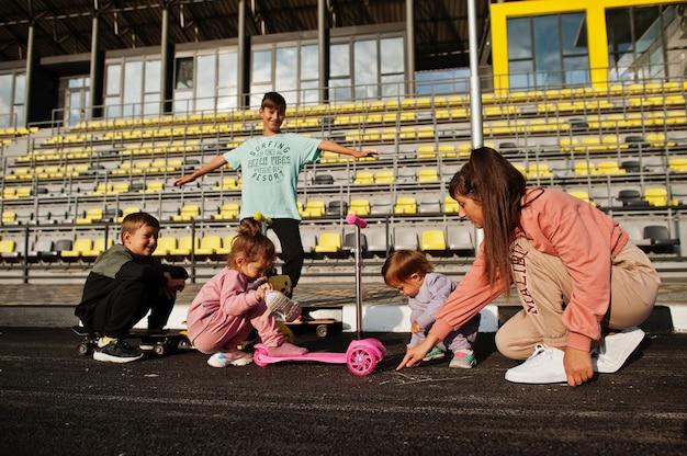 Giovane madre alla moda con quattro bambini all'aperto. la famiglia sportiva trascorre il tempo libero all'aperto con scooter e pattini. dipinto con gesso sull'asfalto.