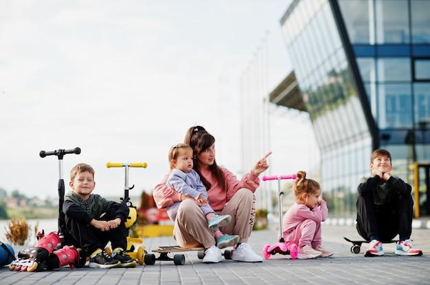 Giovane madre alla moda con quattro bambini all'aperto. la famiglia sportiva trascorre il tempo libero all'aperto con scooter e pattini.