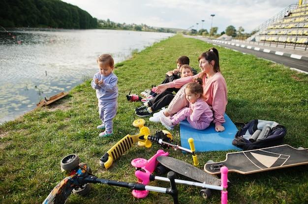 Giovane madre alla moda con quattro bambini che si siedono sull'erba contro il lago. la famiglia sportiva trascorre il tempo libero all'aperto con scooter e pattini.