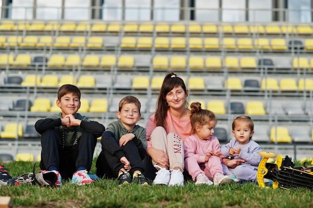 Giovane madre alla moda con quattro bambini che si siedono sull'erba contro lo stadio. la famiglia sportiva trascorre il tempo libero all'aperto con scooter e pattini.