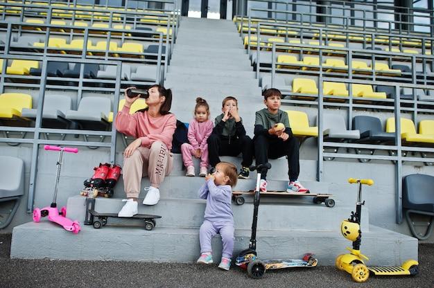 Giovane madre alla moda con quattro bambini seduti sul podio sportivo allo stadio, mangia mela e beve acqua. la famiglia trascorre il tempo libero all'aperto con scooter e pattini.