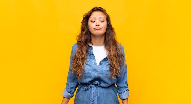 Giovane donna graziosa alla moda su sfondo giallo