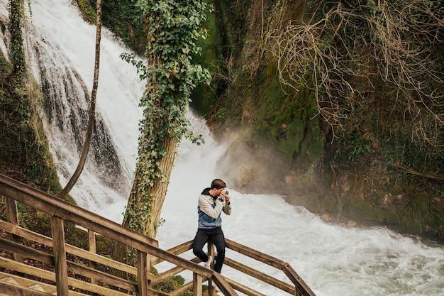 Il giovane turista alla moda sta fotografando la cascata.