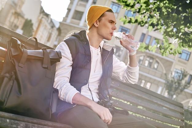 Il giovane blogger turistico alla moda sta bevendo acqua mentre è seduto in panchina
