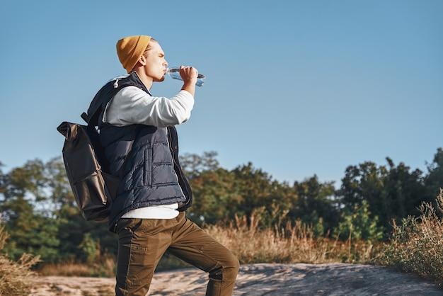 Il giovane blogger turistico alla moda sta bevendo acqua mentre cammina in montagna