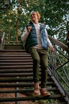 Il giovane blogger turistico alla moda in cappello arancione è sui gradini del parco nazionale. vista posteriore, stagione primaverile, stile casual gratuito