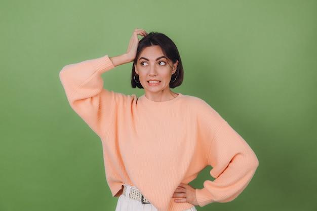 Giovane donna alla moda in maglione pesca casual e occhiali arancioni isolati sul muro verde oliva preoccupato mettere la mano sulla testa guardare da parte copia spazio