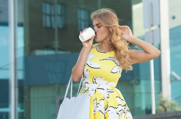 Giovane donna alla moda che beve caffè per andare in una strada cittadina