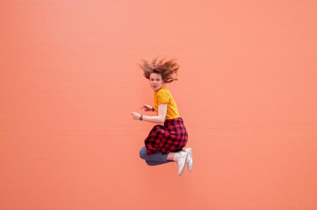 Giovane donna alla moda che salta, balla e si diverte