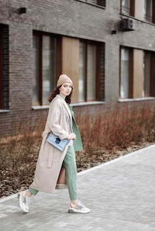 Giovane modella alla moda sulla scena del paesaggio urbano della strada in cappotto e cappello