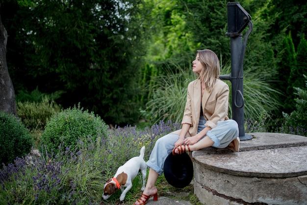 Giovane donna alla moda che si siede vicino ai fiori della lavanda in un giardino