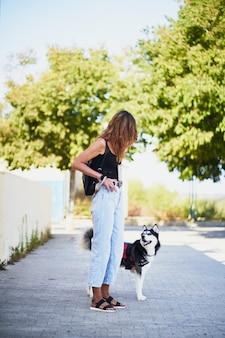 La giovane donna alla moda sta guardando il suo husky siberiano in città