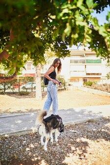Giovane donna alla moda che prende il suo husky siberiano per un giro in park