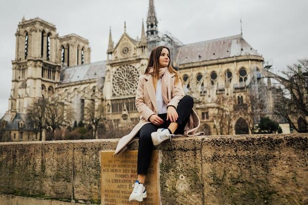 Turista della giovane donna alla moda che si siede vicino alla cattedrale famosa di notre dame a parigi, francia.