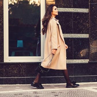 Giovane donna alla moda che cammina in strada. donna che indossa cappotto alla moda, scarpe alla moda e tiene in mano una borsa nera. blogger femminile di moda che va a fare shopping. moda, lifestyle, shopping