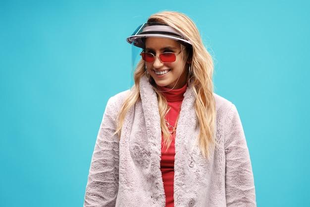 Giovane donna alla moda che indossa la visiera su sfondo blu