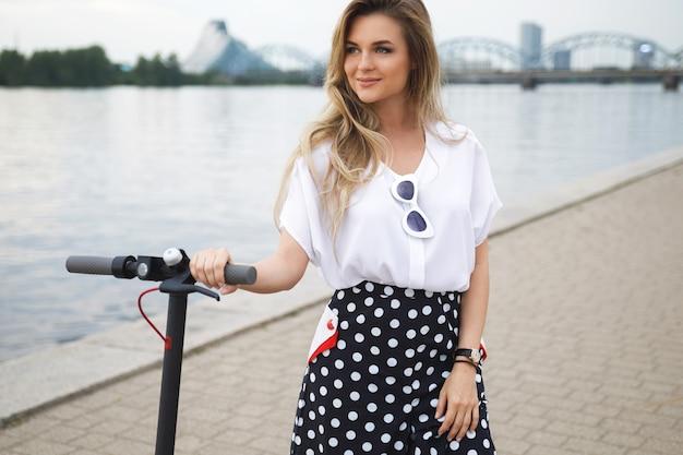 Donna giovane ed elegante con scooter elettrico in riva al fiume