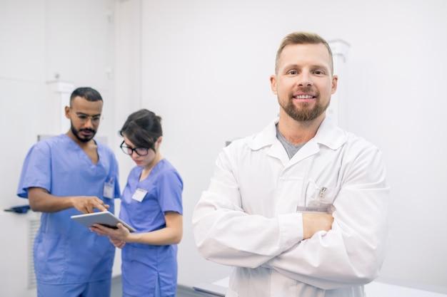 Giovane medico barbuto di successo in whitecoat in piedi davanti alla telecamera con i suoi colleghi che lavorano sullo sfondo