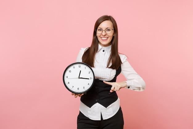 Giovane donna d'affari di successo in tuta e occhiali che punta il dito indice sulla sveglia isolata su sfondo rosa pastello. signora capo. concetto di ricchezza di carriera di successo. copia spazio per la pubblicità.